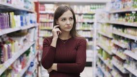 Durchdachte junge hübsche Frau berührt ihr Gesicht, während sie an Entscheidung im Supermarkt denkt stock video