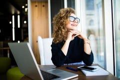 Durchdachte junge Schönheit, die Hand auf Kinn hält und durch ein Fenster beim Sitzen ihrem Arbeitsplatz betrachtet Lizenzfreies Stockfoto
