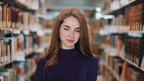 Durchdachte junge Studentin liest ein Buch, das in der Bibliothek steht stock video footage