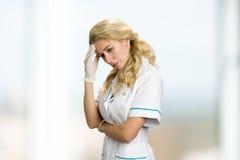 Durchdachte Jungekrankenschwester, Hand auf Kopf Stockbilder