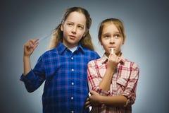 Durchdachte Mädchen der Nahaufnahme mit dem Schule-suppliesat lokalisiert auf Grau Lizenzfreie Stockfotos