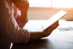 Durchdachte männliche Person, die zum digitalen Tablettenschirm beim Sitzen im modernen Dachbodeninnenraum dem Tisch betrachtet Stockbild