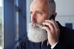 Durchdachte männliche Unterhaltung am Telefon beim Fenster heraus schauen Stockbilder