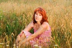 Durchdachte mittlere gealterte Frau auf Wiese Stockfoto