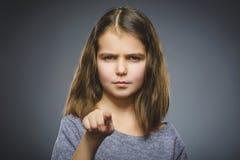 Durchdachte oder verächtliche Mädchenshow der Nahaufnahme an der Kamera lokalisiert auf Grau Stockfoto