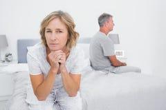 Durchdachte Paare, die auf verschiedenen Seiten des Betts hat ein DIS sitzen Lizenzfreie Stockfotografie