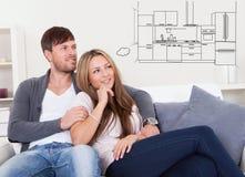 Durchdachte Paare, die an Haben der modernen Küche denken Stockfoto