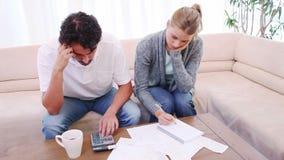 Durchdachte Paare, die ihre Rechnungen zählen stock footage