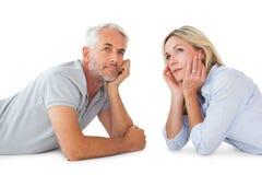 Durchdachte Paare, die oben liegen und schauen Stockfotos