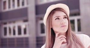 Durchdachte recht blonde Frau gegen das Gebäude Stockbild