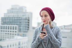 Durchdachte recht blonde Versenden von SMS-Nachrichten draußen Stockfotografie