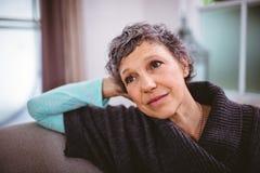 Durchdachte reife Frau, die auf Sofa sitzt Lizenzfreie Stockfotos