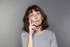 Durchdachte schöne Frau 50s, die unglücklich schaut Stockfoto