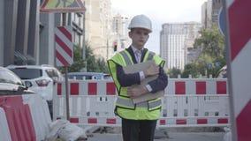 Durchdachte Schutzausrüstungs- und Erbauersturzhelmholding-Bauplanstellung des kleinen Jungen tragende auf einer verkehrsreichen  stock video footage