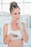 Durchdachte sportliche blonde Versenden von SMS-Nachrichten Lizenzfreie Stockfotografie