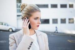 Durchdachte stilvolle Geschäftsfrau, die einen Telefonanruf hat Stockbild