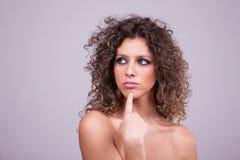 Durchdachte und schöne Frau mit dem lockigen Haar stockbild