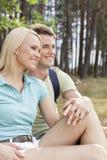 Durchdachte wandernde Paare, die bei der Entspannung im Wald weg schauen Stockfoto