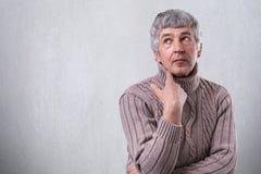 Durchdachter älterer Mann, der über etwas schaut träumt, hochhalten seine Hand unter dem Kinn, das gegen leere weiße Wand mit Kop Lizenzfreie Stockbilder