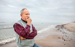 Durchdachter älterer Mann, der auf dem Strand steht lizenzfreie stockbilder