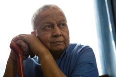 Durchdachter älterer Mann, der gehenden Stock beim Sitzen am Pflegeheim hält Stockfotografie