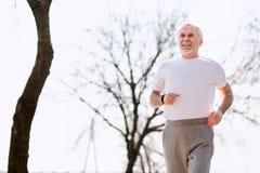 Durchdachter älterer Mann, der im Park aufwärmt stockfotografie