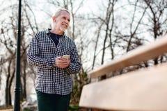 Durchdachter älterer Mann, der Musik wählt stockfoto