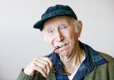 Durchdachter älterer Mann in einem Hut und in den Gläsern Lizenzfreies Stockbild