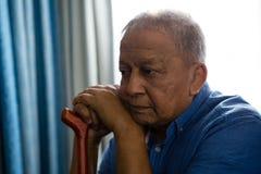 Durchdachter älterer Mann mit dem gehenden Stock, der durch Fenster im Pflegeheim sitzt Lizenzfreies Stockbild