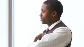 Durchdachter afroer-amerikanisch Geschäftsmann mit den gefalteten Armen im Büro stock footage