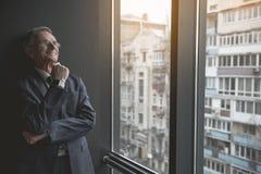 Durchdachter alter Geschäftsmann, der an der Straße aufpasst lizenzfreies stockbild
