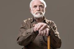 Durchdachter alter Mann mit Spazierstock lizenzfreies stockbild