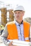 Durchdachter Architekt, der weg schaut, beim Halten an der Baustelle entwirft Stockbilder