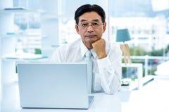 Durchdachter asiatischer Geschäftsmann, der die Kamera betrachtet Lizenzfreies Stockfoto
