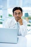 Durchdachter asiatischer Geschäftsmann, der die Kamera betrachtet Stockfotos