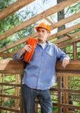 Durchdachter Bauarbeiter Carrying Rolled Stockbild