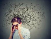 Durchdachter betonter junger Mann mit einer Verwirrung in seinem Kopf stockfotografie