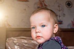 Durchdachter Blick eines kleinen Kindes, welches heraus das Fenster schaut Stockbild