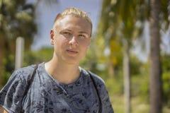 Durchdachter blonder Jugendlicher mit seinem Haar oben gebunden Lizenzfreie Stockfotos