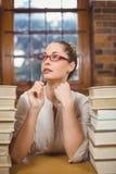 Durchdachter blonder Lehrer, der zwischen Büchern in der Bibliothek sitzt Lizenzfreies Stockfoto