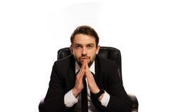 Durchdachter Chef, der an seinem Schreibtisch sitzt Stockfotografie