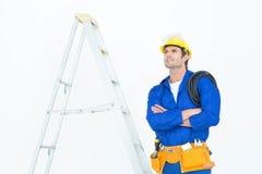 Durchdachter Elektriker mit den Armen gekreuzt durch Leiter Stockbild