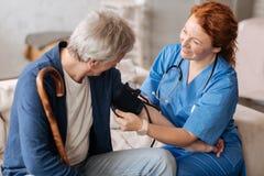Durchdachter erfahrener Doktor, der tonometer für Maße einsetzt Lizenzfreies Stockfoto