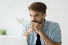 Durchdachter ernster Mann verlor in den Gedanken vor Laptop lizenzfreie stockfotos