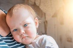 Durchdachter flüchtiger Blick des Kindes gedrängt zu seiner Großmutter ` s Brust Lizenzfreie Stockfotos
