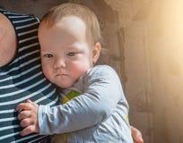 Durchdachter flüchtiger Blick des Kindes gedrängt zu seiner Großmutter ` s Brust Stockbild