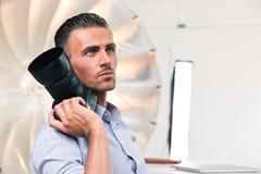 Durchdachter Fotograf, der Kamera hält Stockbild