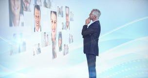 Durchdachter Geschäftsmann, der eine Wand abgedeckt durch Profilbilder betrachtet Lizenzfreie Stockfotos