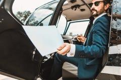Durchdachter Geschäftsmann, der im Hubschrauber sitzt und die Dokumente verwahrt lizenzfreie stockbilder
