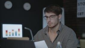 Durchdachter Geschäftsmann, der mit Dokument nahe Computer im dunklen Büro arbeitet stock video